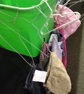 This image shows several items clinging to their hangers for dear life, their hangers knocked askew.